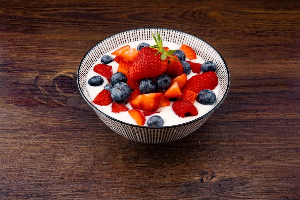 bowl of yogurt with strawberry and blackberries on top of brown table